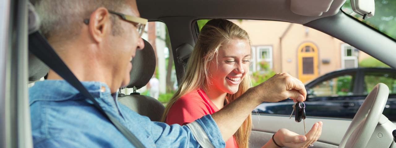 Dad handing car keys to teen