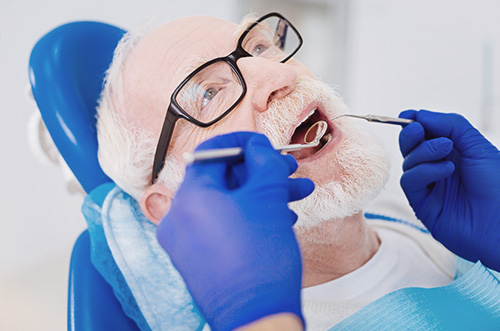 A patient getting a dental exam from a dentist.